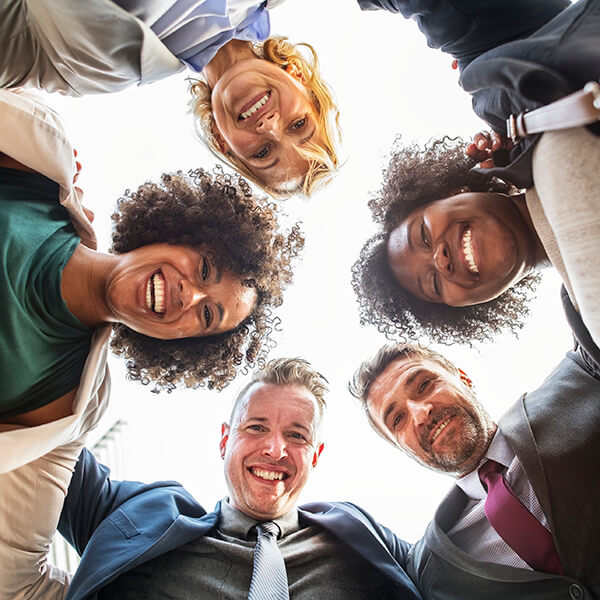 A huddle of diverse business professionals smiling and looking downward to wards the center.