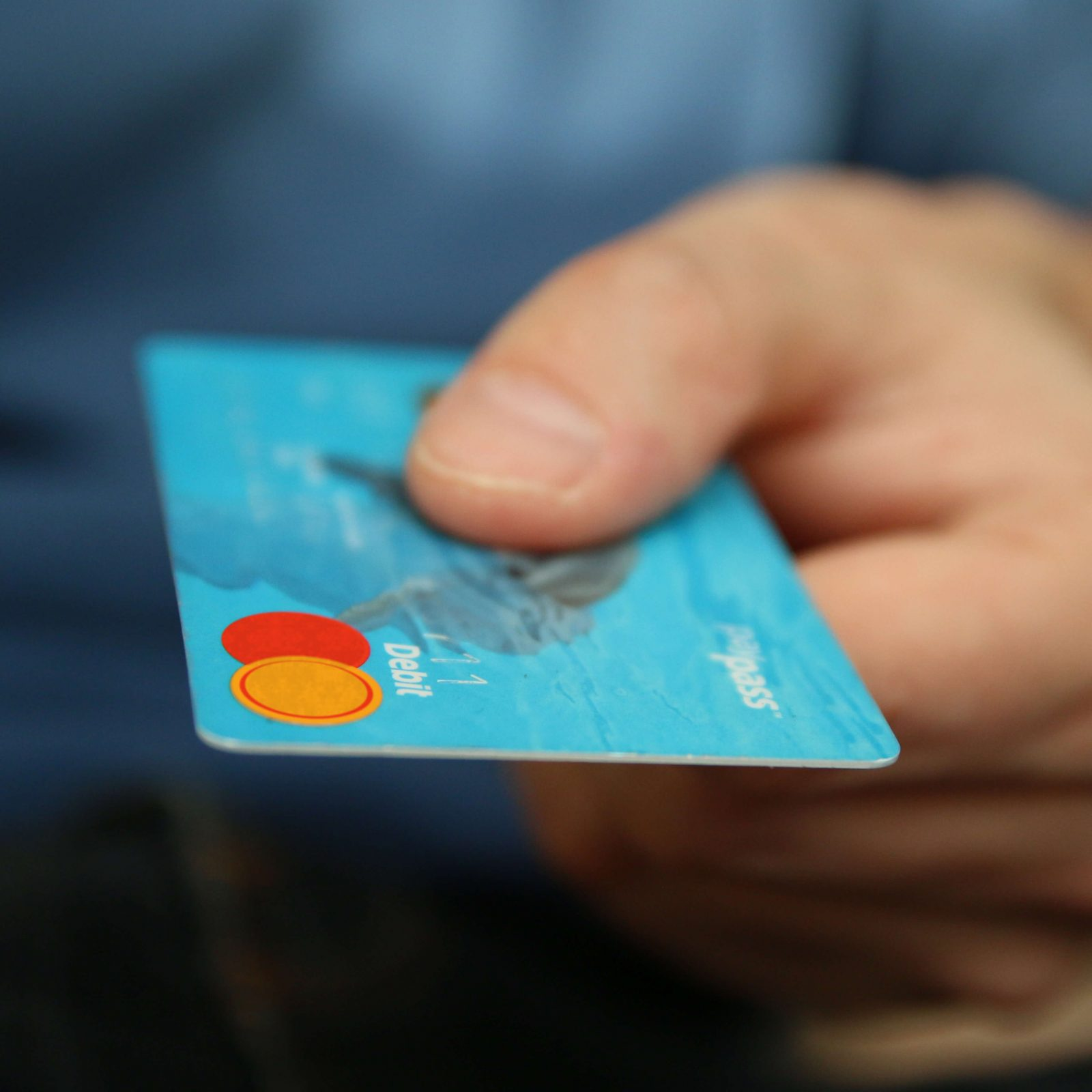A hand reaching out and handing out a debit card with their thumb covering the card numbers.