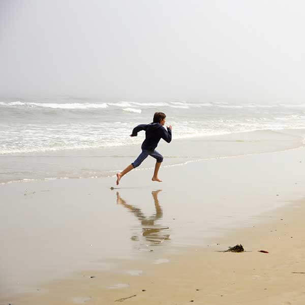 A young woman wearing jeans and a hoodie running on the shoreline of a cold beach.