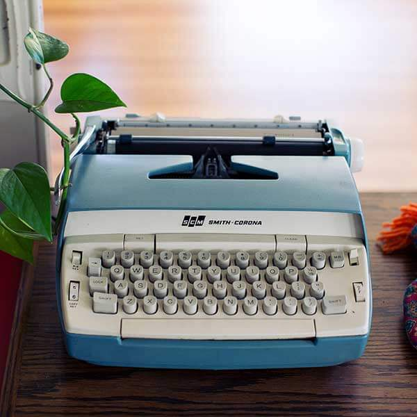A vintage typewriter with raised buttons sitting on a wooden table with a vine growing from its side.