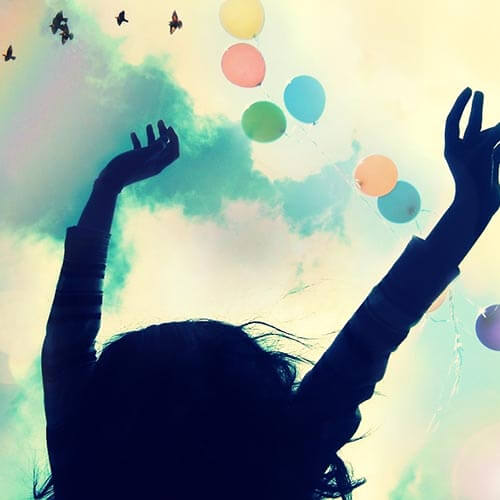 Silhouette of a woman with their hands up and colorful balloons flying in the sky above.