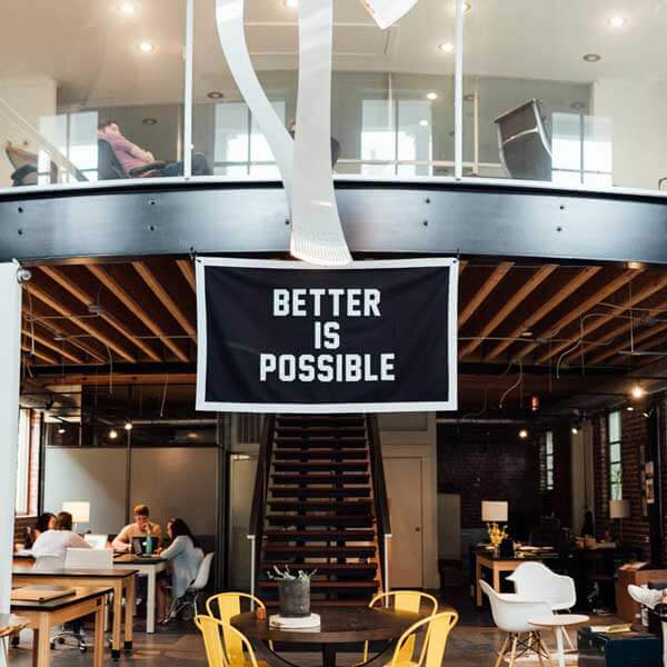A modern office with many open chairs and tables with a banner across the entrance saying better is possible.