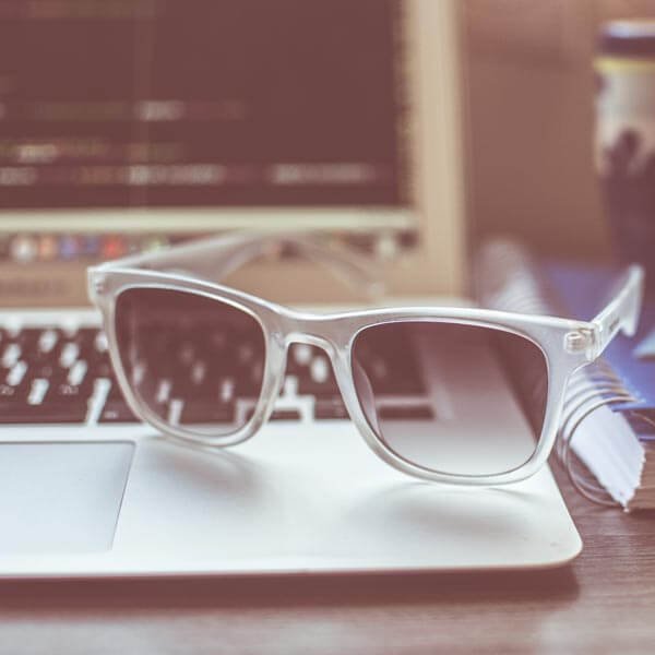 A laptop with sunglasses resting on the keyboard with clear frames and lightly tinted shades.