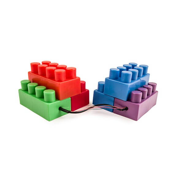 Two brick Lego toy sets sitting side-by-side with a black chord connecting the two.