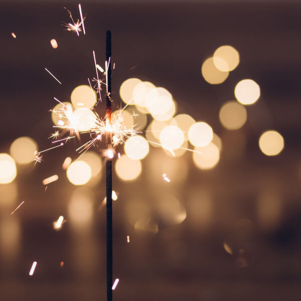 The tip of an ignited sparkler shining brightly against a night sky.