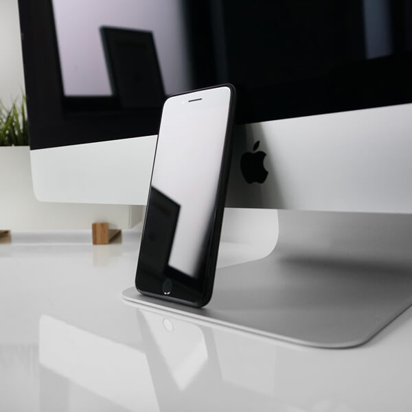 A zoomed in photograph of an Apple Computers monitor and an iPhone resting on it.