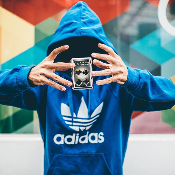 A magician wearing a large Adidas brand hoodie floating a stack of cards with his hands.